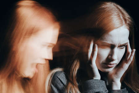 Sick woman with schizophrenia hearing voices. Blurred face on black background. Stock Photo