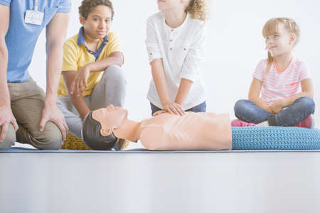 Low angle of kid performing cpr on manikins chest and trainer giving instruction of first aid