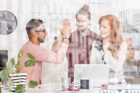Spaanse man en team leiden met een high five in business office