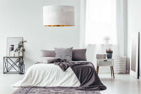 Big, white lamp above simple bed with gray cushions and blanket in bright bedroom interior with window, patterned rug and nightstand