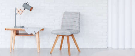 Lamp and cloth on wooden table next to grey chair against white brick wall with copy space in living room interior