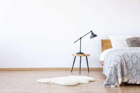 Empty white bedroom interior with wooden floor and bed with blanket, stool with a lamp and fur rug Reklamní fotografie