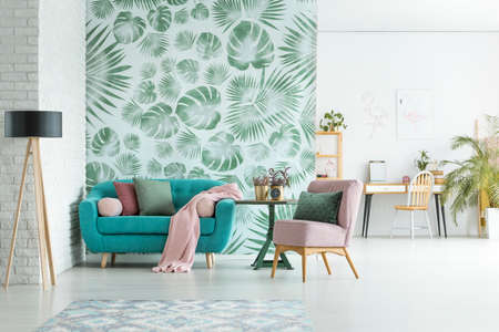 Turquoise lounge with pink blanket and pillows standing in stylish apartment interior with floral wallpaper Stock Photo