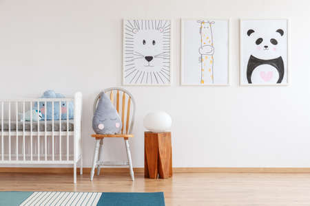 Cute grey raindrop shaped cushion placed on wooden chair standing next to white crib in bright baby room interior