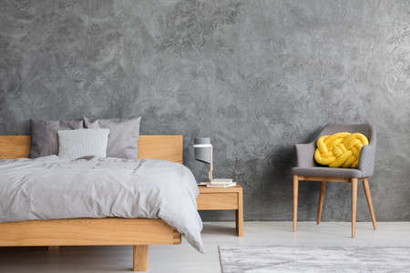 Grey bedroom interior with king size bed, armchair and yellow knot cushion 版權商用圖片