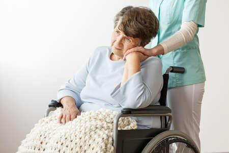 Sad disabled senior woman sitting in a wheelchair in nursing house