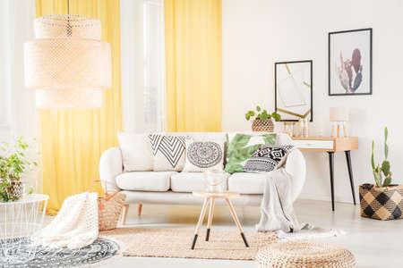 ボヘミアンなリビングルームのインテリアで居心地の良いソファに横たわるパターンの枕 写真素材 - 94127454