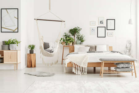 White and beige bedroom interior with plant on wooden stool and brazilian chair hanging next to the bed 版權商用圖片
