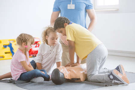 African-american boy pressing manikins chest during first aid training in school with lifesaver