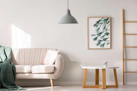 manta en el sofá beige cerca de la mesa de madera contra la pared blanca con el cartel en el interior del apartamento con la escalera y la lámpara gris Foto de archivo
