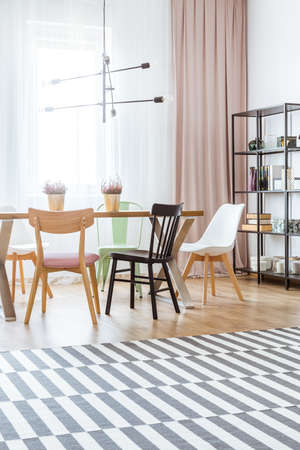 Black and white chair at wooden table with heathers in gold pots in bright dining room interior with patterned carpet