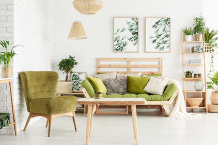 Green armchair next to wooden table in floral living room interior with lamps and pillows on a sofa against white wall with leaves posters Фото со стока