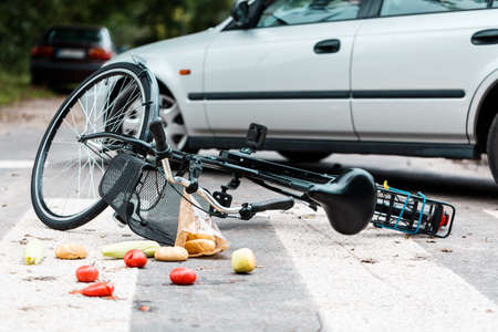 Crashed bike lying on the street near a car after traffic accident