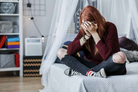 Rebellious girl crying on bed because of unhappy teenage love Foto de archivo