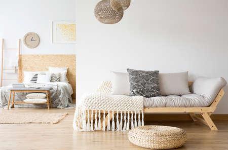 リビングルームにグレーのソファ、ベッドルームに木製ベッドが備わり、モダンなアパートメントのオープンデザイン