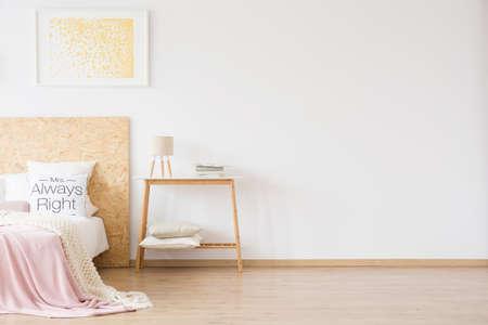 Chambre féminine avec des points d'or peinture remise au-dessus du lit avec tête de lit en bois et couverture rose
