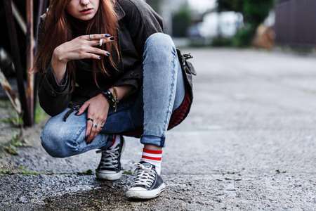 Close-up of riotous young girl smoking cigarette on the sidewalk
