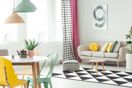 Wooden stool and pouf on black and white geometric carpet next to settee in cozy apartment interior with pastel chairs at table