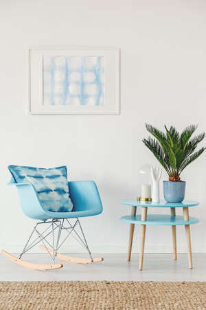 Palm on blue table next to rocking chair with cushion against white wall with poster in apartment interior with brown carpet