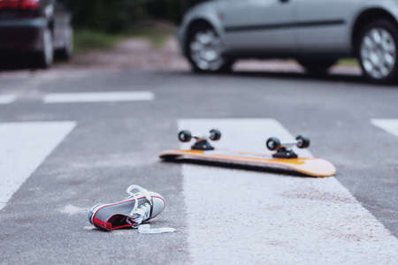 Teenagers shoe and skateboard lying on a pedestrian crossing after traffic accident