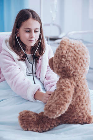 Sick girl examining a teddy bear with a stethoscope in hospital bed