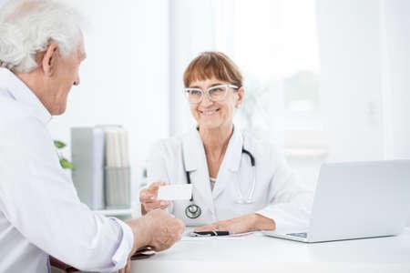 그녀의 환자에게 다음 약속 세부 정보가있는 여성 의사 스톡 콘텐츠