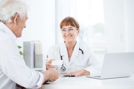 Female doctor giving her patient a card with the next appointment details