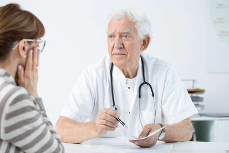Worried doctor announcing bad news to his patient after medical examination