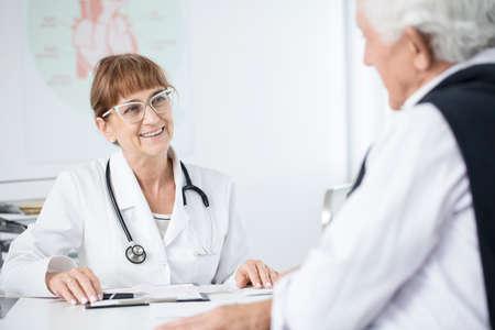 Elder doctor with glasses smiling at her patient after medical examination 写真素材