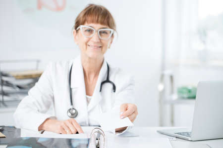 Elder oculist with glasses holding a prescription for glaucoma medicine Foto de archivo