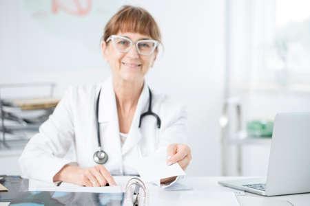 Elder oculist with glasses holding a prescription for glaucoma medicine Stockfoto