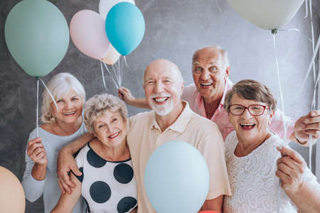 Close-up of happy, excited pensioners during a birthday party, holding colorful balloons. Active seniors concept. Stock Photo