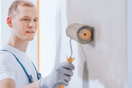 Specialist worker using a paint roller with a yellow handle to paint the walls beige