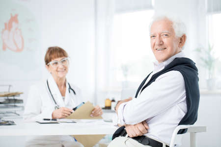 Senior man sitting at the doctors office and smiling after hearing good news