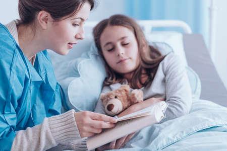 Oudere zus lezen van een boek aan een ziek meisje met knuffel in privékliniek