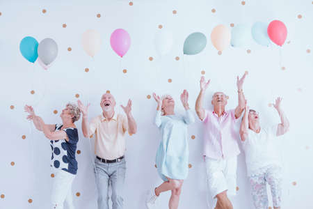 Excited elderly men and women having fun at a birthday party with colorful balloons Reklamní fotografie