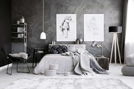 White and black lamp in grey bedroom interior with boxes and drawings on concrete wall above bed Stok Fotoğraf