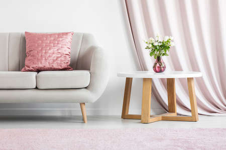Pink pillow on beige sofa next to a wooden table with roses in bright living room interior Stock Photo