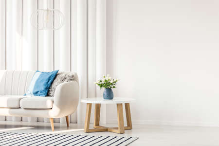 Stock Photo   White Wooden Table Next To Sofa With Blue Cushion In Empty  Wall Living Room Interior
