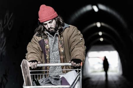 En primer plano, un vagabundo desesperado con carro buscando refugio en el paso subterráneo. Persona borrosa en el fondo