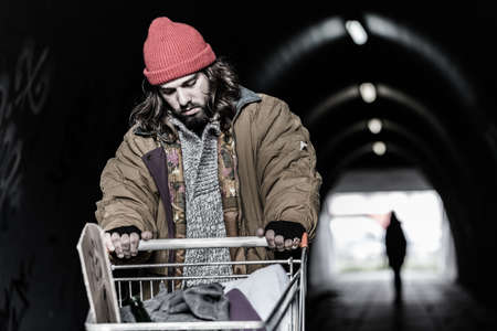 In the foreground hopeless drifter with trolley looking for shelter in the underpass. Blurred person in the background Foto de archivo