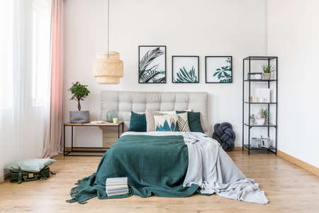 Grey and green blanket on bed against white wall with posters in bedroom interior with plant and lamp
