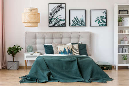 Rattan lamp above bed with green bedding and grey bedhead in bedroom interior with leaves posters Stockfoto