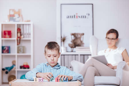 In the foreground, autistic child playing with colorful cubes and counselor observing his behaviors in the background