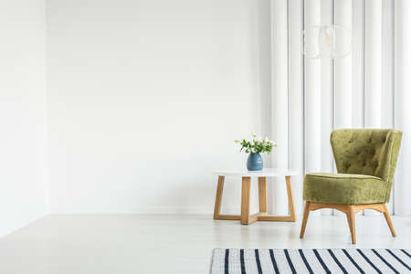 White living room interior with green armchair next to a wooden table and empty wall