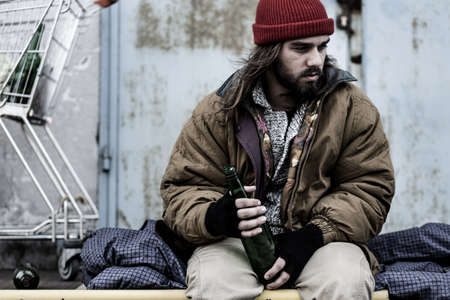 Dirty and depressed alcoholic holding a bottle. Alcoholism and homelessness concept Standard-Bild