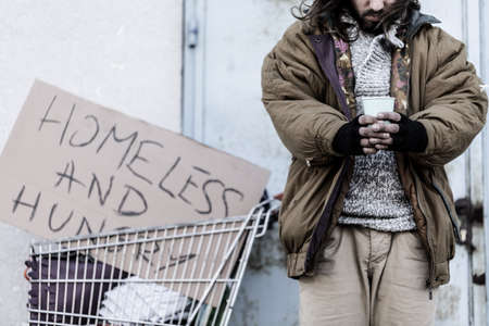 Close-up of homeless and hungry vagrant holding a cup, asking for money and food
