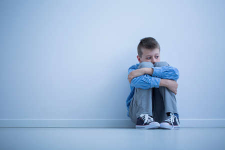 Young boy with hypersensitivity sitting alone on the floor against the wall with copy space 스톡 콘텐츠
