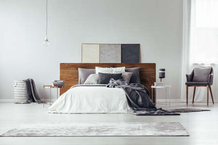 Dark bedsheets on bed with wooden bedhead and beige rug in bright bedroom interior with lamp on table next to armchair