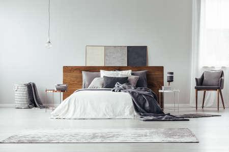 Dunkle Bettwäsche auf Bett mit hölzernem Bettkopf und beige Wolldecke im hellen Schlafzimmerinnenraum mit Lampe auf Tabelle nahe bei Lehnsessel